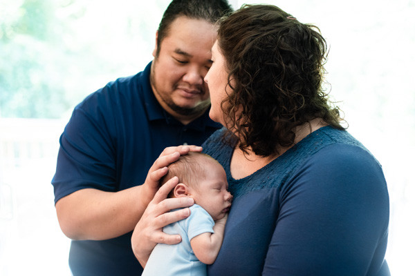 In-home lifestyle photography session with both parents embracing newborn baby in Charlotte NC