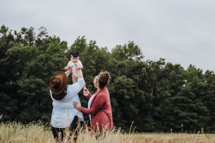A lesbian couple outdoors in a field tossing their 6 month old daughter in the air.