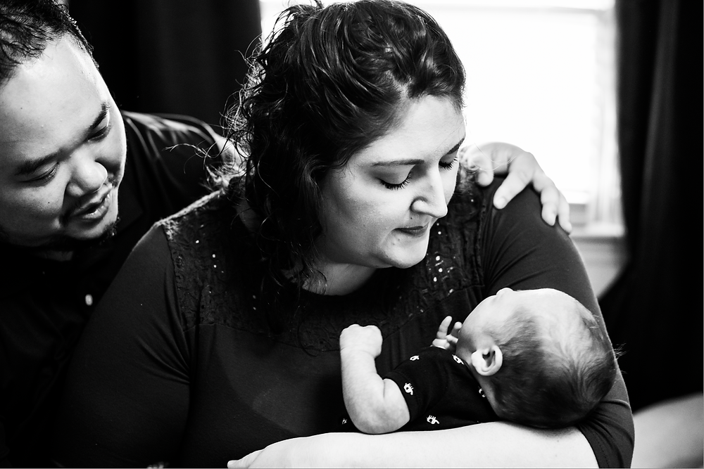 Black and white in-home lifestyle newborn photography session with mother and father cradling newborn son in nursery