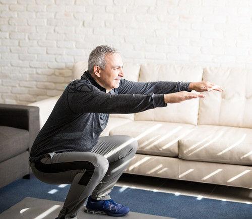 Image of a senior man doing squats at home.