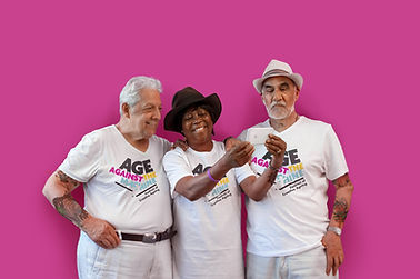 Three senior citizens stand in front of a pink wall. They are taking a selfie. All three wear t-shirts reading 'Age Against the Machine'.