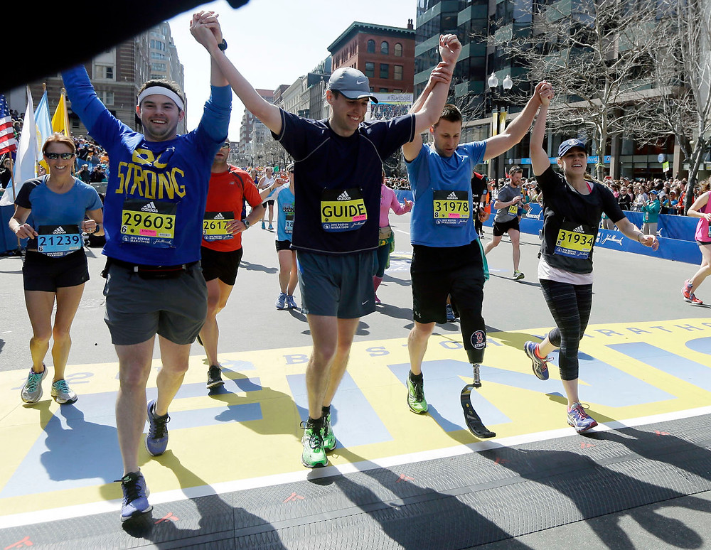 Patrick Downes crosses the finish line at the Boston Marathon (WBUR.org)
