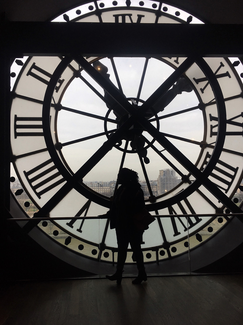 female silhouette in front of clock in paris france