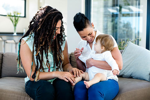 Lesbian couple playing with their baby i