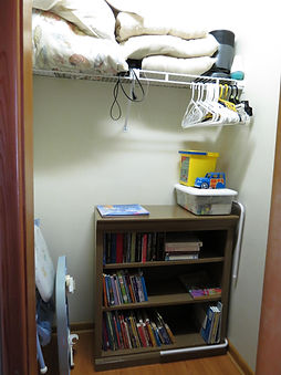 upstairs bedroom has high chair, bed rail, toys, books and more