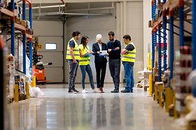 Workers with supervisors at warehouse with consultant