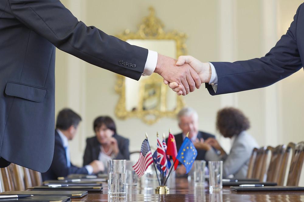 Poignée de main autour d'une table. Petits drapeaux de plusieurs pays sur la table.