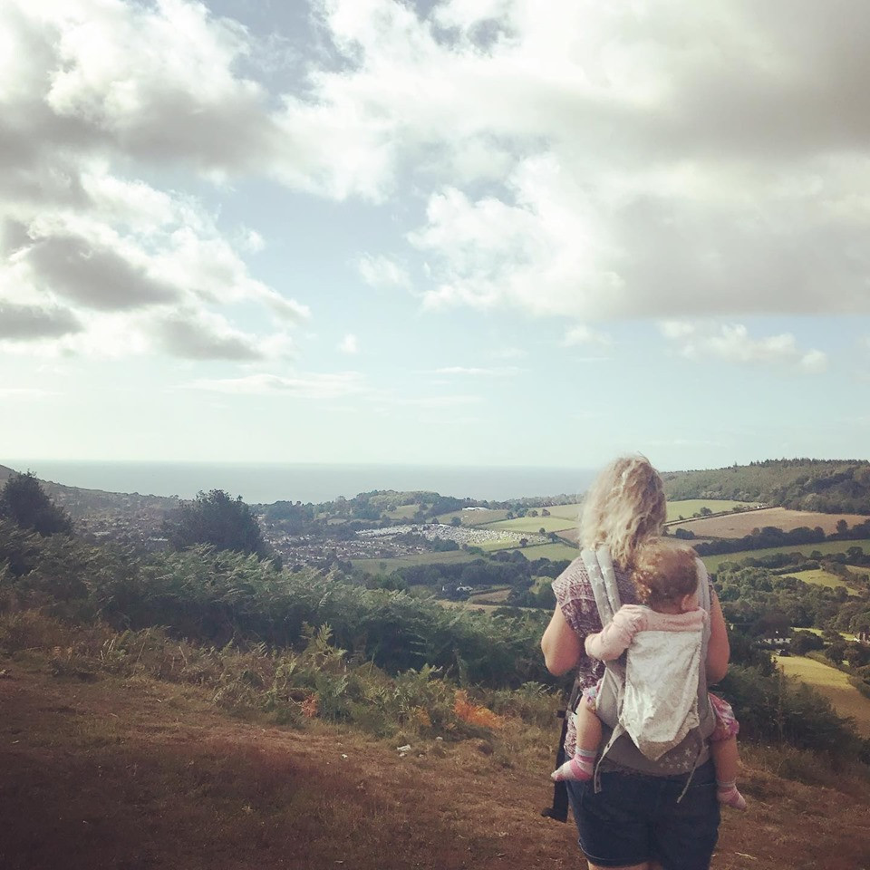 Carrying a baby in an ergo carrier looking out over a valley of fields and woodlands, out to the ocean.