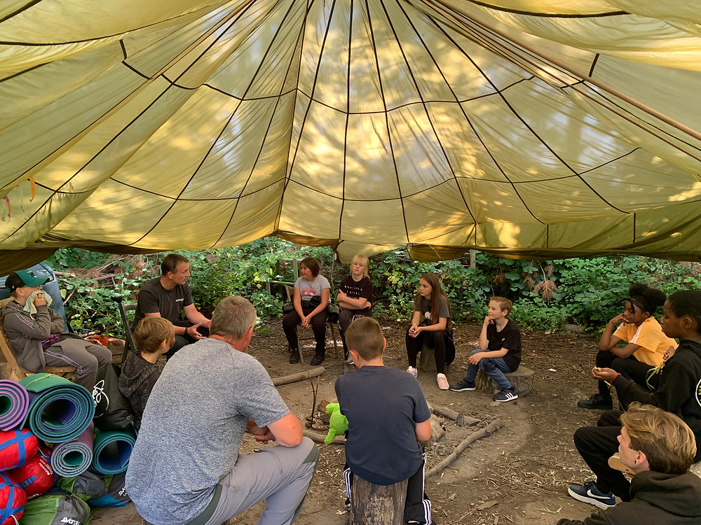 A photo of Will Benson of Kids Kabin telling stories round the campfire
