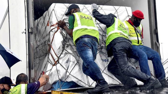 Os trabalhadores carregam as primeiras doses de vacina contra a doença coronavírus da África do Sul