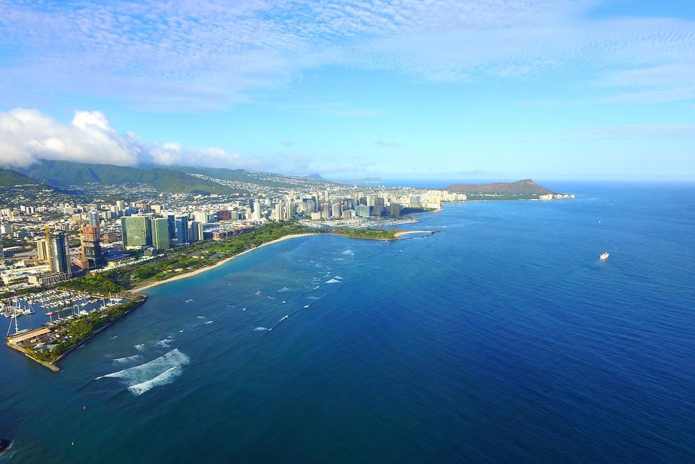 画面左端に写っているのがダイビングのボートが出港するKewalo Basin Harbor。真ん中のビーチはアラモアナビーチ。そしてその奥に隣接しているビル群がワイキキ。この目の前の海が格好のダイビングポイントになっています。その奥に鎮座しているのがダイヤモンドヘッド  (PHOTO/Tomohito Ishimaru)