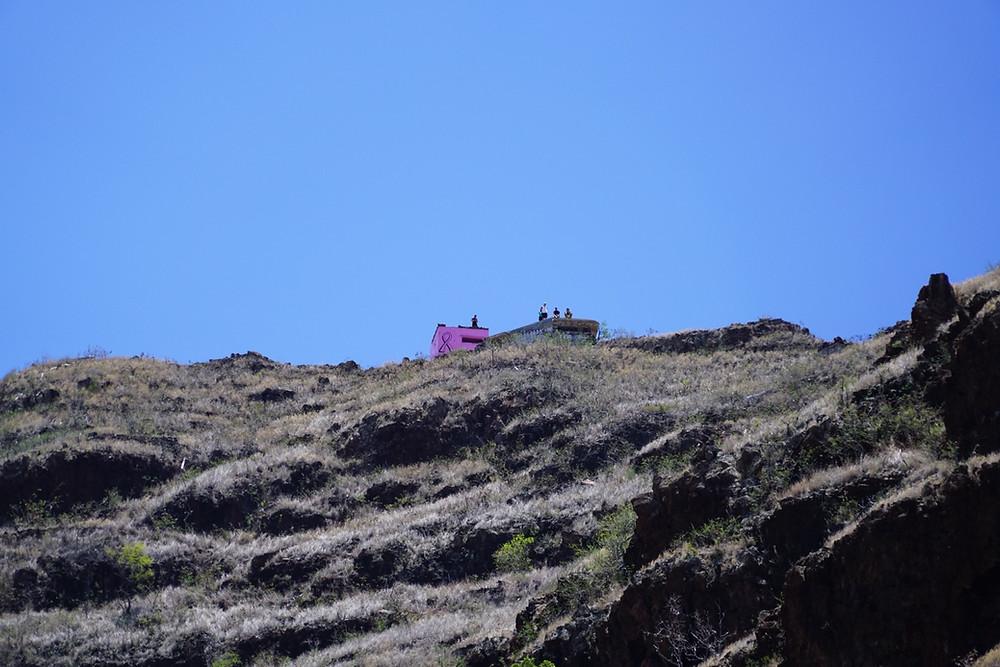 登り口から見上げると、ピンクピルボックスはすでに見えます。これはかなりの望遠レンズ(240mm)で撮っているので、実際にはもっと遠くに見えます。登った日(8/20)は土曜日なので、頂上はローカルたちで賑わっている模様  (PHOTO/Tomohito Ishimaru)