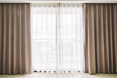 Tan coloured curtains half open in an apartment window.