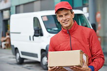 Smiling male postal delivery courier man outdoors  in front of cargo van delivering package.jpg
