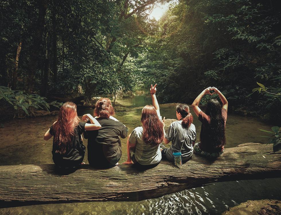 Canva - Five Women Sitting On Tree Trunk