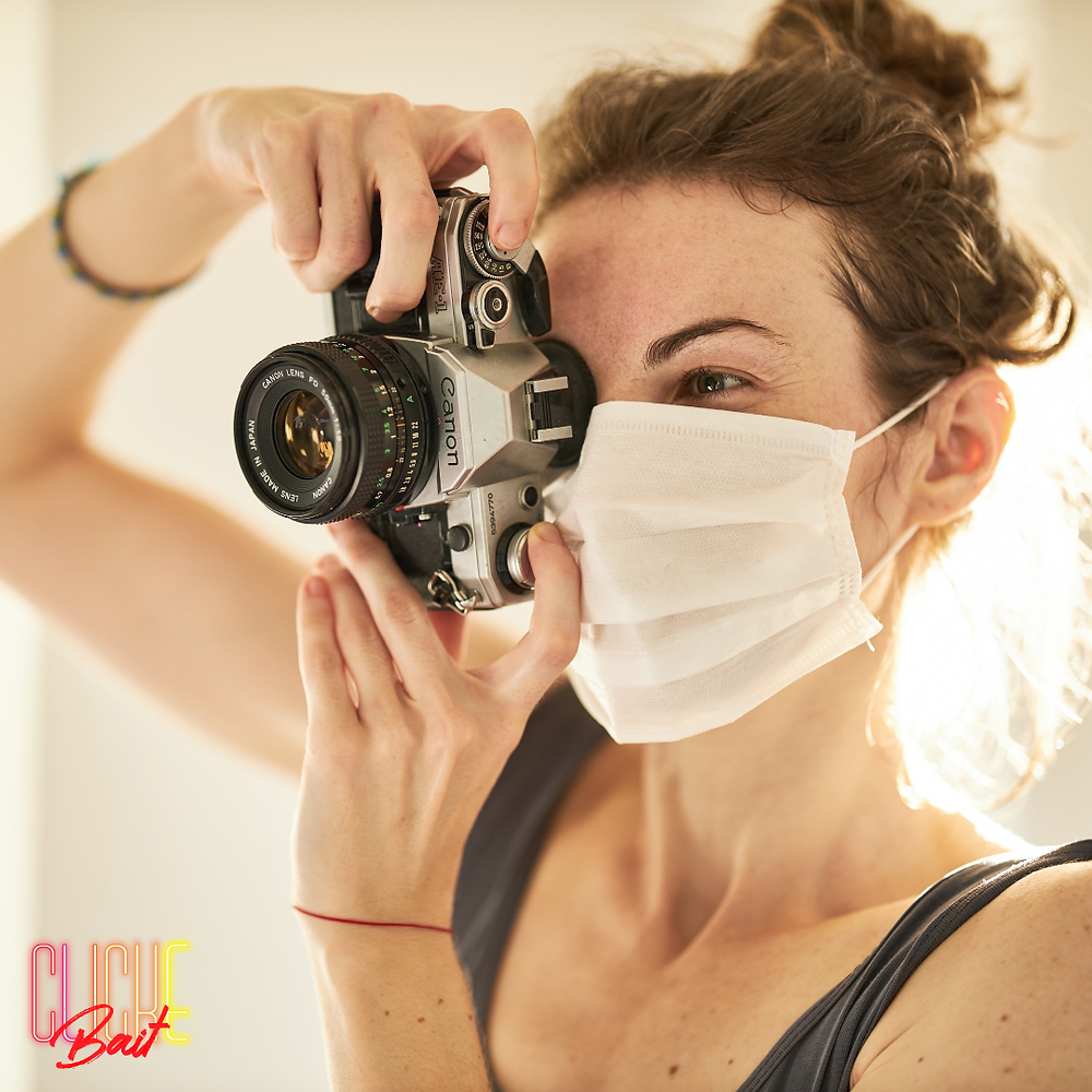 Woman taking a picture with digital camera wearing a surgical mask