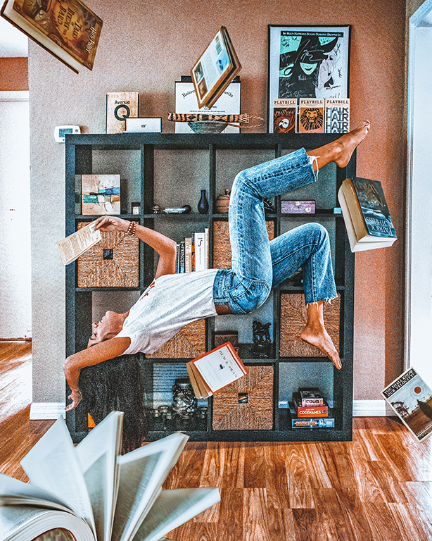 Woman suspended in the air along floating books