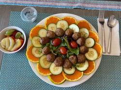 Meatballs served with salad and cucumbers