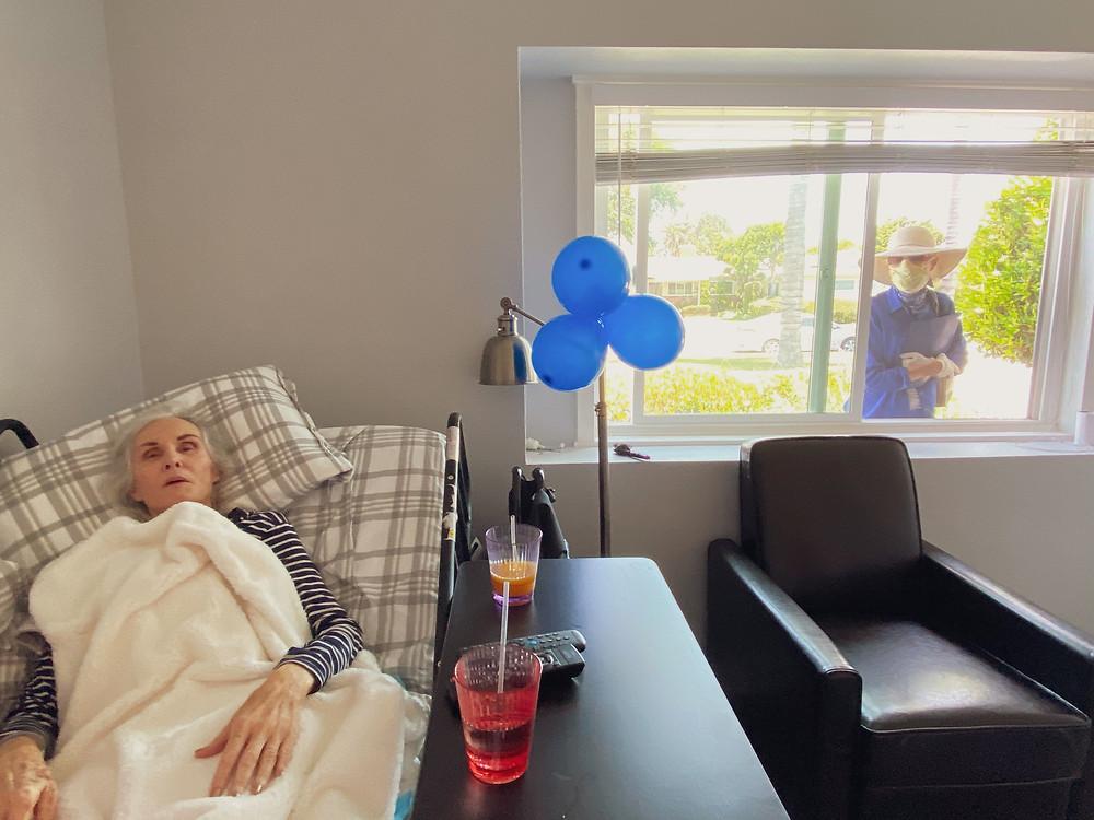 Relative visiting her elderly family member through a window.