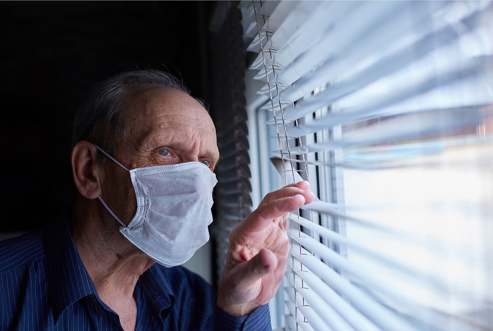 Elderly man looking out the window.
