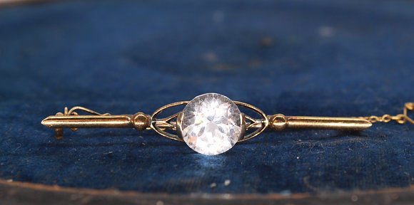 A 18ct gold bar brooch set with a clear stone, 6cm wide, weighing 5.8g