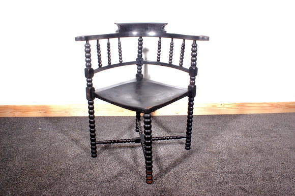 A 19th century ebonised elm smokers bow corner chair