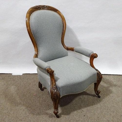 A Victorian walnut-framed open-arm fireside chair