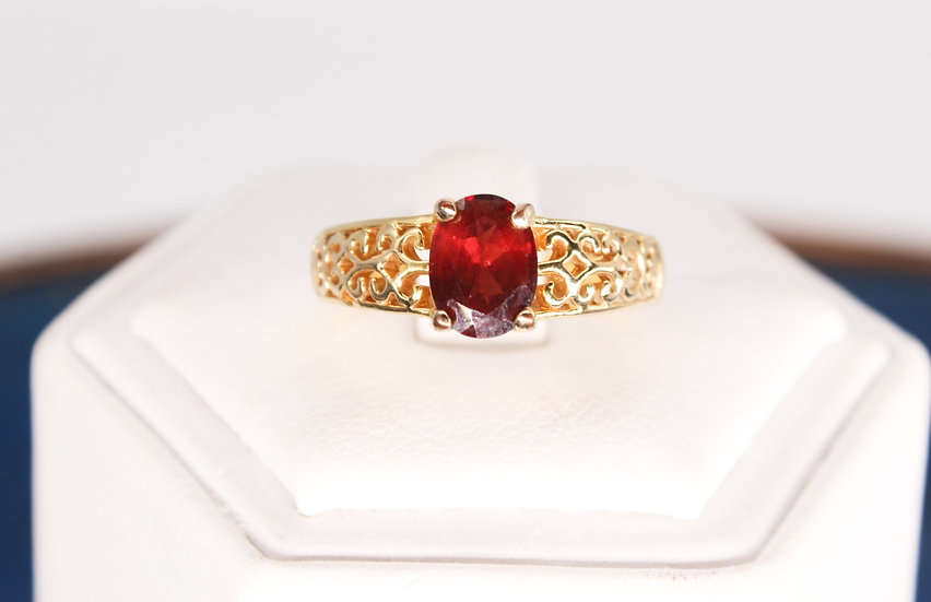 A gold coloured metal red stone ring with ornate pierced shoulders, size N