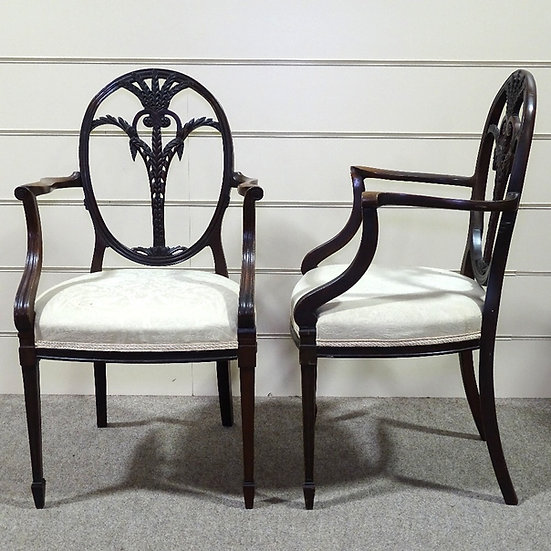 A pair of late 19th century mahogany Sheraton style elbow chairs