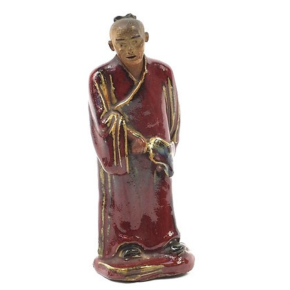 Chinese porcelain figure of a monk having a sang de boeuf glaze