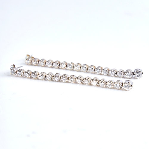 A pair of unmarked white gold graduated diamond line pendant earrings