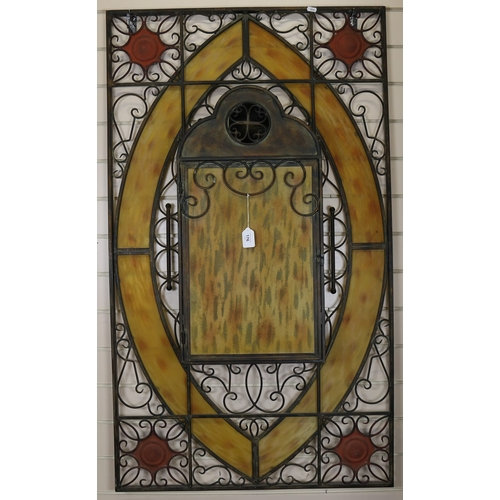 A large wrought-iron and yellow stained glass candle stand wall panel