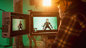 Director Looks at Displays Directs Green Screen CGI Scene with Actor Wearing Motion Tracki