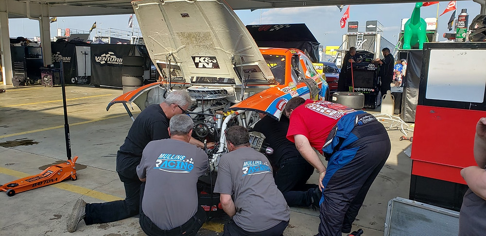 Willie Mullins looking over his crew, Tony Furr, Robert Bruce, Al Chewing and Greg Purkey make repairs to his County Waste Crow Wing Recycling Ford Fusion at Charlotte Motor Speedway