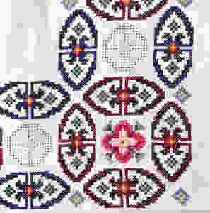 Detail from a vintage hand-embroidered table cloth with round designs.  Cross stitch and whitework