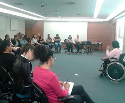 Descrição da imagem: participantes estão ao lado esquerdo observando a debatedora Fabíola Fernanda do Patrocínio Alves, que se encontra ao lado direito. Todos estão sentados.