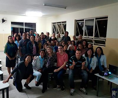 Descrição da imagem: participantes estão em uma sala sorrindo.