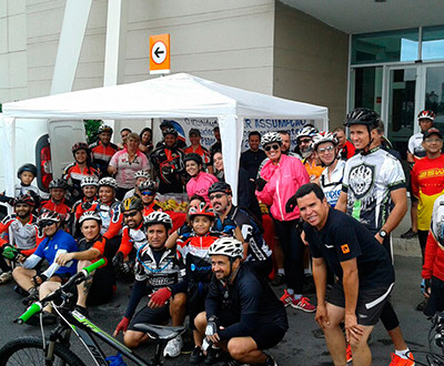 Descrição da imagem: participantes estão em frente ao shopping. A maioria usa capacete e roupas próprias para o ciclismo. Todos estão sorrindo.