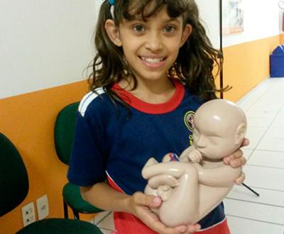 Descrição da imagem: criança sorri e segura um material em formato de feto.