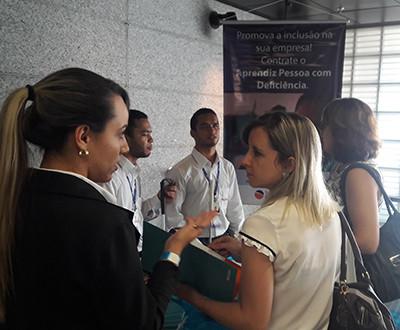 Descrição da imagem: três funcionários do Instituto Ester Assumpção estão explicando o trabalhado desenvolvido pela organização para duas participantes.