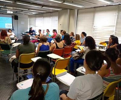 participantes estão sentados e de costas, observando Fabíola Fernanda do Patrocínio Alves, coordenadora de Pesquisa e Projetos do Instituto Ester Assumpção.