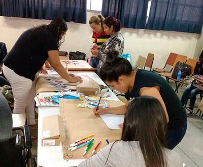 Descrição da imagem: 5 mulheres estão produzindo material pedagógico.