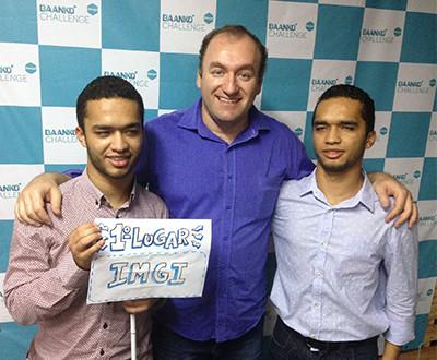 Descrição da imagem: Romário, Oswaldo e Ricardo estão de pé sorrindo. Romário segura uma plaquinha com os dizeres: primeiro lugar | IMGI.