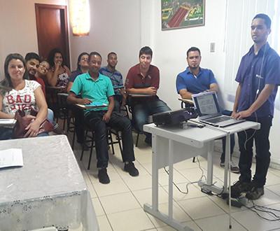 participantes estão sentados em cadeiras e Ricardo está de pé.