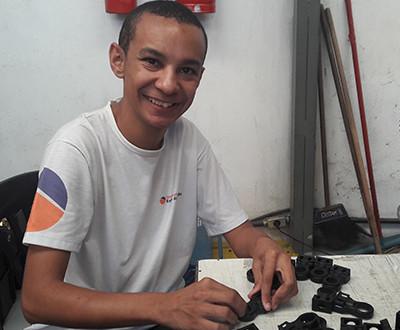 Lucas usa uniforme da cor branca e está sorrindo. Ele está em seu ambiente de trabalho.