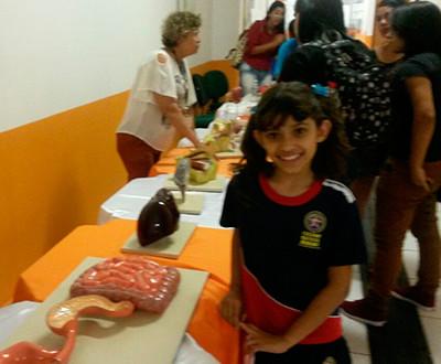 Descrição da imagem: foto da exposição. Há visitantes conversando com a expositora e uma criança sorrindo.