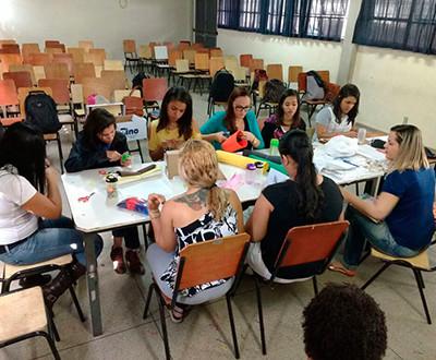 participantes estão sentados em cadeiras apoiados em uma mesa retangular produzindo materiais pedagógicos.
