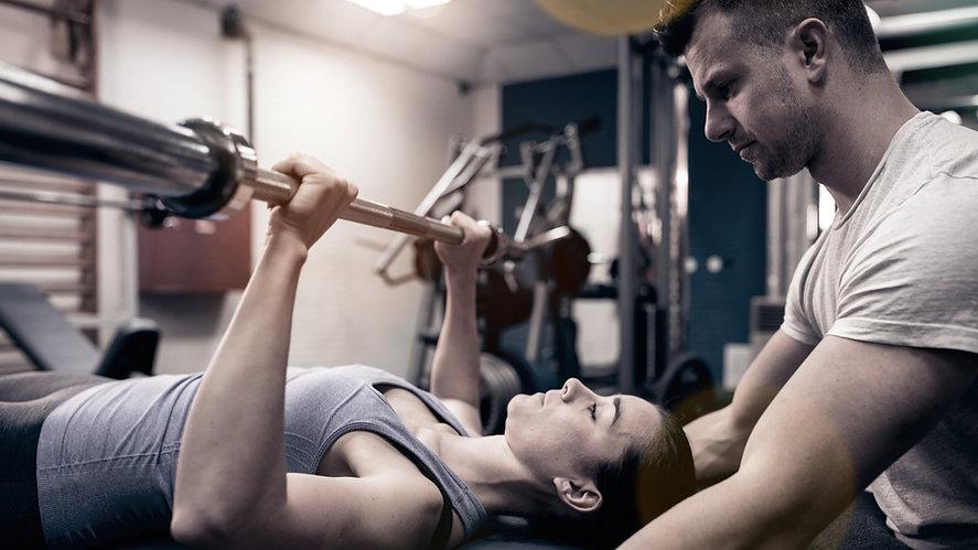 Femme qui soulève des poids accompagnée d'un coach