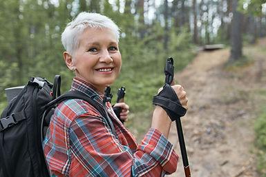 femme en exterieur avec baton de marche
