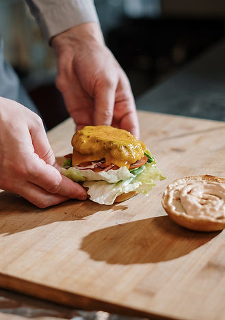 person-holding-burger-on-brown-wooden-ch